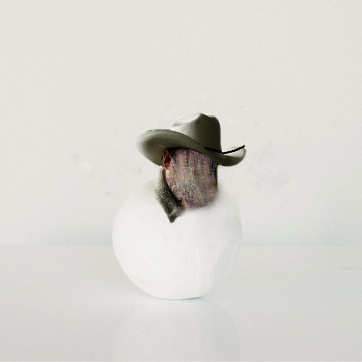 A picture of the head a cowboy sitting on a smooth round white stone.